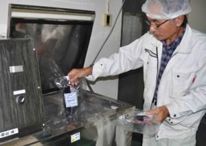 真空パックした切り身を液体急速凍結機に投入する与論町漁協の箕作参事=17年12月、同漁協