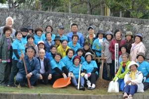 両陛下の来島を記念し、トックリキワタを植樹した「パナウルゆいまぁる会」のメンバー=23日、与論町