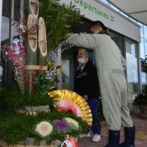 門松を設置する施設利用者=26日、奄美空港