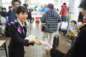 鹿児島線45周年で到着客に記念品を手渡すJAC職員ら=1日午前、沖永良部空港