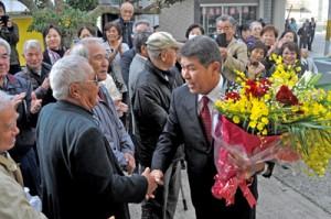 多くの町民や職員に出迎えられ、笑顔で初登庁する今井力夫町長=21日、知名町