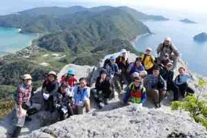 ミヨチョン岳の絶景を背景に記念撮影する参加者=10日、瀬戸内町請島(同町提供)