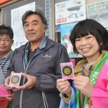 知名町のマンホールカードを最初に入手した平さん(中央)=9日、おきのえらぶ島観光協会