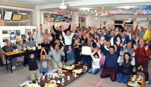 天皇杯と表彰状を囲み万歳する校区住民=10日、平田集落公民館
