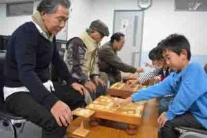 対局を楽しむ児童と囲碁将棋クラブの会員=25日、宇検村地域福祉センターやけうちの里