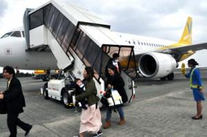 関西国際空港から奄美空港に到着したバニラ・エアの初便と搭乗客ら=3月26日、奄美市笠利町