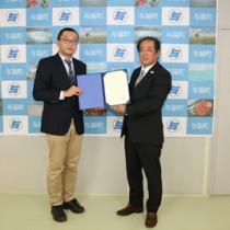 日本サンゴ礁学会からサンゴ礁保全奨励賞を受けた田畑理事長(右)=13日、与論町(提供写真)