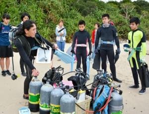 インストラクターから指導を受けダイビングに挑戦した生徒たち=3日、龍郷町の倉崎海岸