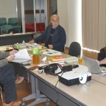 沖永良部島民の集団移住を報告する前利さん(右)。説明に耳を傾ける座談会参加者=15日、知名町