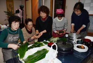 カシャ餅づくりを体験する「この指とまれ・つながり逢いの会」の会員ら=22日、奄美市住用町