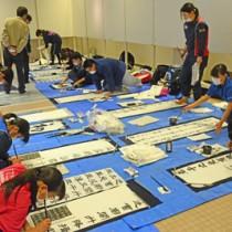 5校47人が参加した揮毫大会=17日、奄美市名瀬