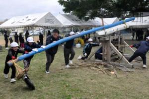 昔ながらのサタグルマを使ったサトウキビ搾りを体験した児童ら=25日、伊仙町喜念小学校