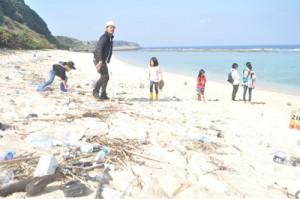 海岸に漂着したごみの種類を調査する参加者=21日、知名町の沖泊海浜公園