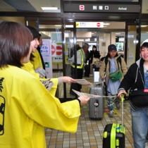成田線の到着客にシマ博パンフレットを手渡す観光関係者=31日、奄美市笠利町の奄美空港