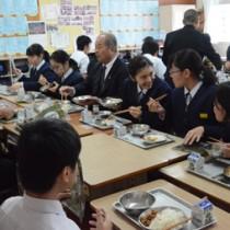 福山副市長(中央)と魚汁や豚みそなどの郷土料理を給食で楽しむ生徒たち=23日、奄美市の朝日中学校