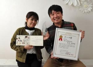 二つのコンテストで入賞した秋津さん(写真右)=31日、徳之島町亀津