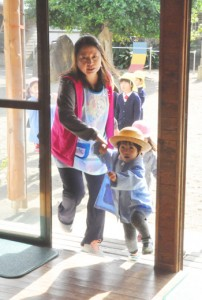 防災行政無線を聞いて、建物へ避難する園児ら=10日、徳之島町亀津