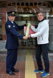 夜光反射材を受け取る宗監督(右)=9日、奄美警察署