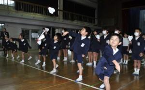 自分で作った紙飛行機を飛ばす児童=29日、知名町の下平川小学校体育館
