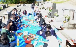 墓前で酒席を囲み、先祖とともに新年を祝う人々=16日、知名町田皆