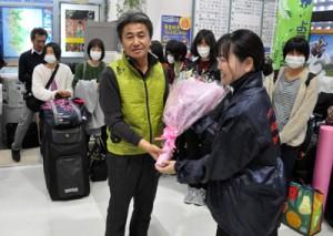 合宿で来島した日本実業団女子長距離関係者を代表し歓迎の花束を受け取った永山監督=17日、天城町の徳之島空港