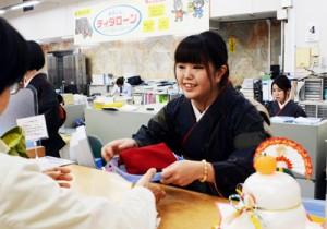 本場奄美大島紬姿で接客に当たる奄美大島信用金庫の女性職員=4日、奄美市