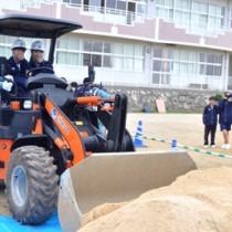 建設機械の操縦を体験する生徒=19日、知名中学校グラウンド