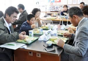 地場産野菜を使った給食を味わった生産者らと児童=16日、天城町岡前小学校与名間分校