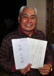 集落内で交流した機動隊員から届いた手紙を手に笑顔の大城さん=6日、和泊町