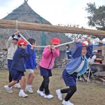 サタグルマを回してサトウキビの汁を搾る児童ら=30日、和泊町の大城小