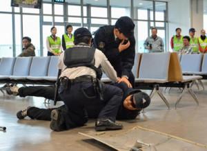 訓練で不法侵入者役を取り押さえる警察官ら=26日、奄美空港の搭乗待合室