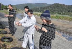 大島紬新商品開発プロジェクトが始動。のり張り作業を行うメンバー=20日、龍郷町戸口