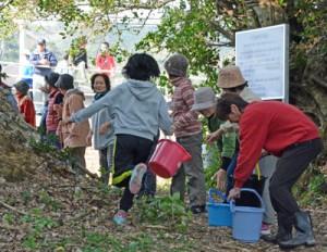 バケツリレーで消火用の水を運ぶ地域住民=21日、奄美市笠利町笠利