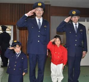 警察官の制服を着て、沖永良部署員らと記念撮影するイベント参加者=8日、和泊町