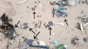 海岸に流れ着いていた黒い油様の物体=1月31日、奄美市名瀬の朝仁海岸(提供写真)