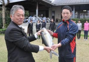 冬季合宿中の実業団チームにカンパチを贈った奄美群島地区漁業士会の田畑会長(左)=8日、天城町与名間