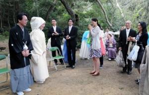 式後、親族や友人から拍手で祝福を受ける水谷淳一さん、里佳さん夫妻(左)=24日、瀬戸内町瀬武の高千穂神社