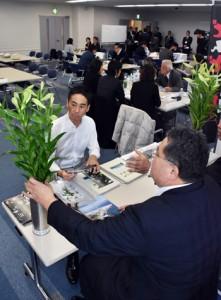 商談会でユリを展示してPRする沖永良部花き専門農協の担当者=8日、鹿児島市