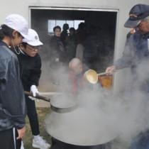 黒糖を入れた鍋のあく取りをする児童=13日、国頭小