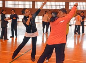 振り付けを指導する小松教授(中央左)ら=24日、旧大島工業高体育館