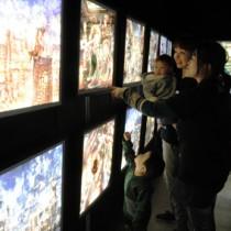 えんとつ町のプペル展点灯式で、光る作品に見入る関係者ら=2日夜、瀬戸内町
