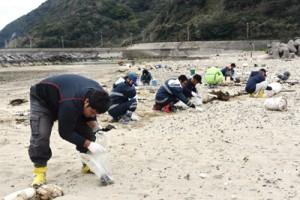 手作業で漂着油の回収を行う参加者=14日、龍郷町嘉渡