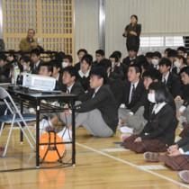 鳥飼さん(左)の話を聞く奄美高校の生徒ら=22日、奄美市名瀬