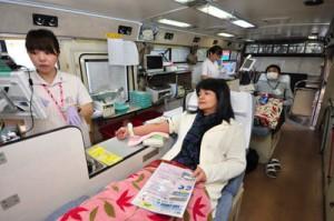 県赤十字血液センターのバス内で献血に協力する住民ら=16日午後、奄美市住用町