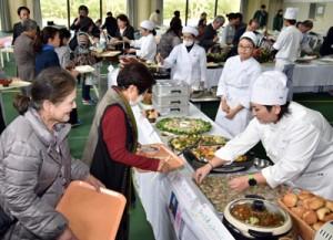 感謝の気持ちを込めて保護者らに料理を提供した学生たち(右)=9日、奄美看護福祉専門学校