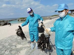 漂着油が絡んだ漁網を回収する参加者=9日、喜界町のスギラビーチ