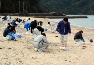 漂着油の回収作業に汗を流す奄美市職員=9日、朝仁海岸