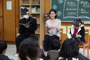 原口さんと一緒に朗読する児童生徒=1月31日、名柄小中(提供写真)