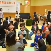 方言のわらべ歌遊びを楽しむ参加者ら=18日、県立奄美図書館