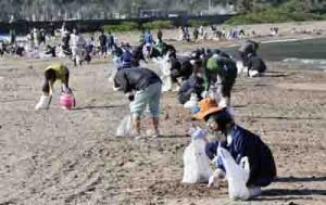漂着油の除去作業を行う住民ボランティアら=18日、奄美市名瀬の知名瀬海岸
